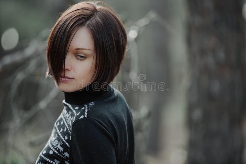 摆在自然的秋天的年轻美丽的逗人喜爱的女孩在s下 免版税库存图片