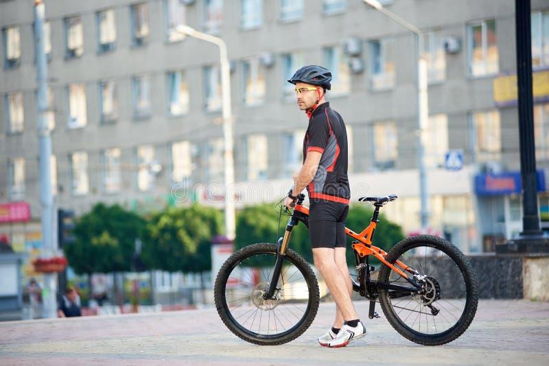 摆在自行车附近的运动的男性骑自行车者在市中心 免版税图库摄影