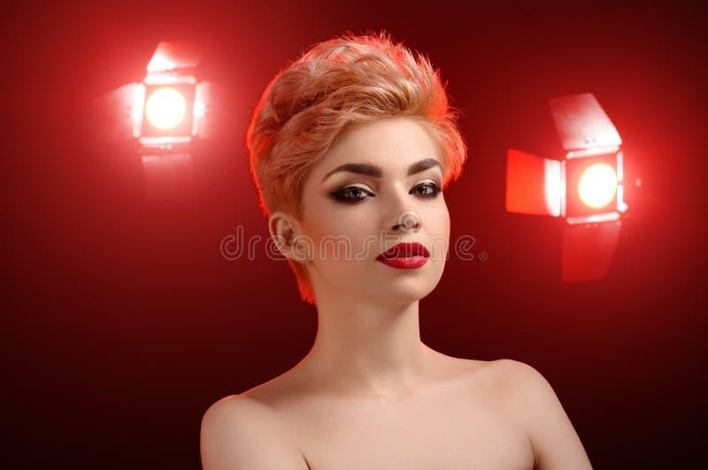 摆在艺术性的红色l的美丽的年轻白肤金发的红色有嘴妇女 免版税库存图片