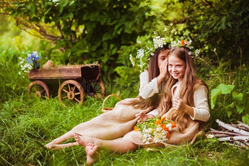 摆在草的一件白色礼服的美丽的小女孩 日落光 库存照片