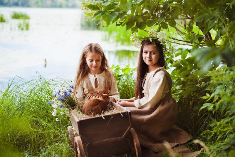 摆在草的一件白色礼服的美丽的小女孩 日落光 库存图片