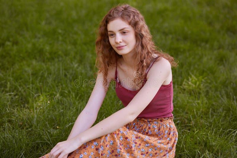摆在草的嫩平安的模型画象开会,看直接,享受休息aftr长的步行,佩带的红顶 免版税图库摄影
