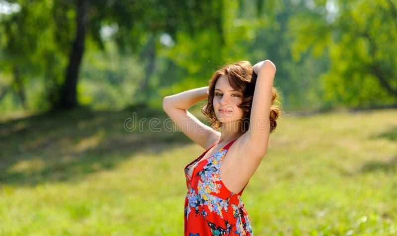 摆在草的红色礼服的年轻深色的女孩在夏天公园在阳光下 免版税库存照片