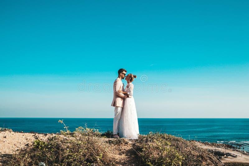 摆在蓝天和海后的峭壁的新娘和新郎 夫妇领巾水晶珠宝附加婚礼 免版税库存照片