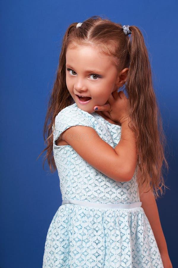摆在蓝色时尚礼服的愉快的做鬼脸的孩子女孩 特写镜头p 免版税库存图片
