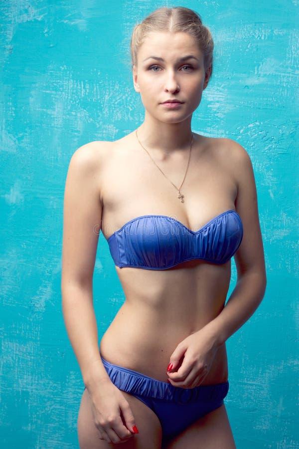 摆在蓝色泳装的女孩的纵向 库存照片