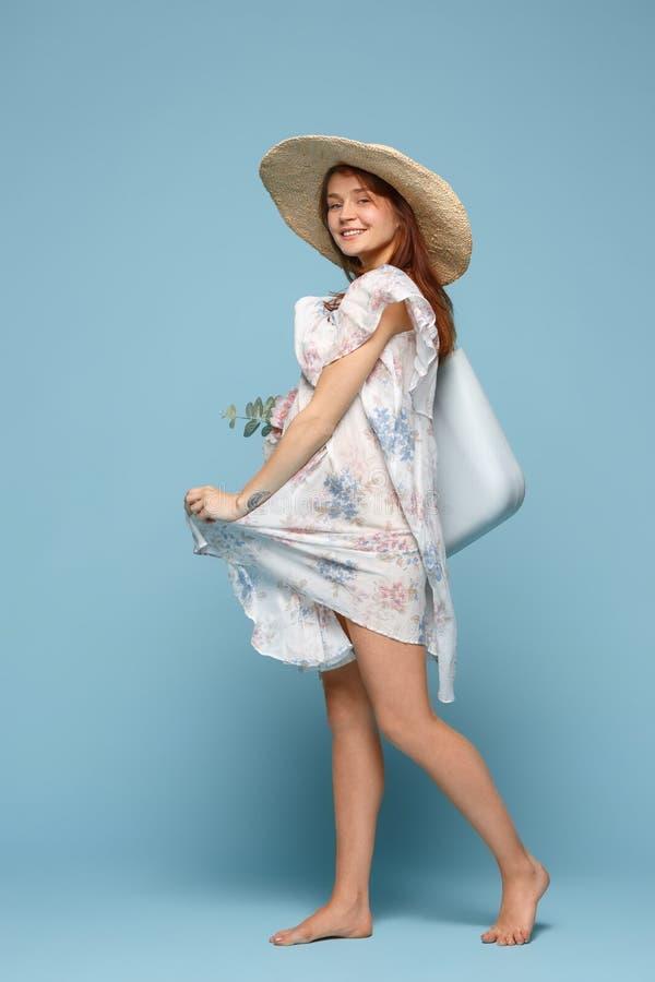 摆在蓝色背景的年轻美丽的孕妇 免版税库存图片