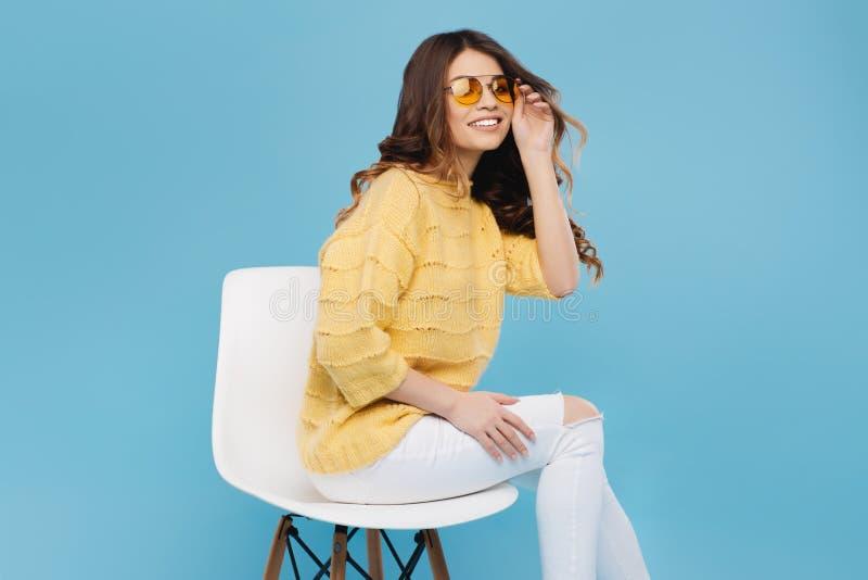 摆在蓝色背景的黄色毛线衣的可爱的少妇 黄色玻璃的俏丽的女孩 免版税库存图片