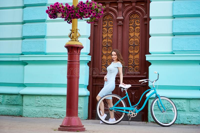 摆在蓝色葡萄酒旁边的微笑的可爱的女孩在与红色古色古香的门的老历史蓝色大厦附近骑自行车 库存照片