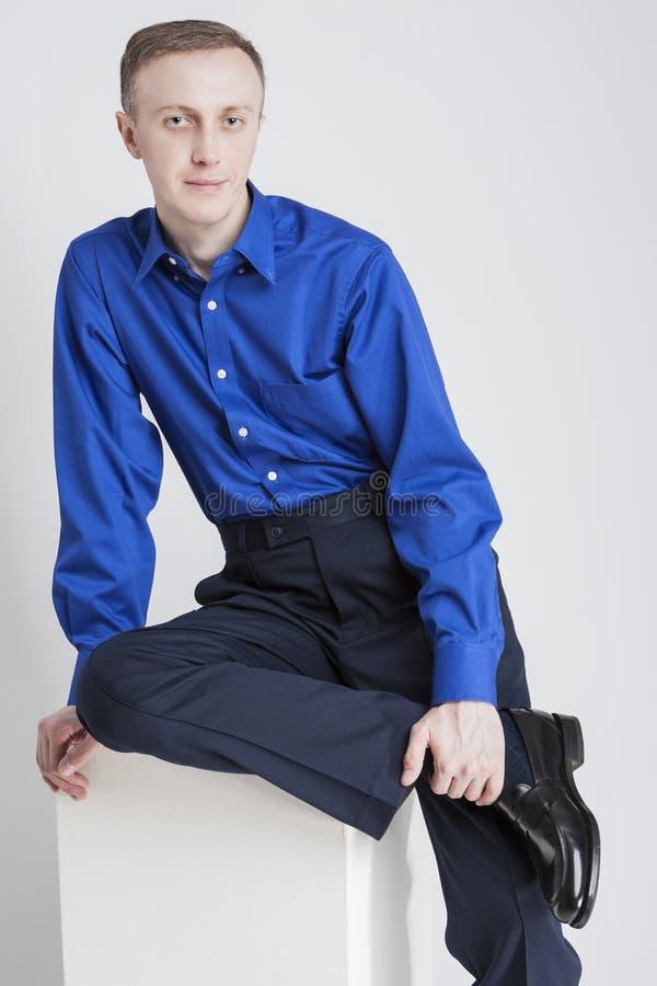 摆在蓝色衬衣和深蓝长裤的英俊的白种人人画象反对白色 免版税图库摄影