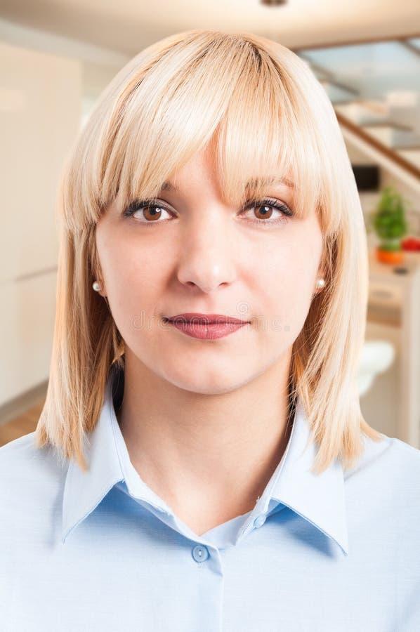 摆在蓝色衬衣的白肤金发的妇女画象 免版税库存照片