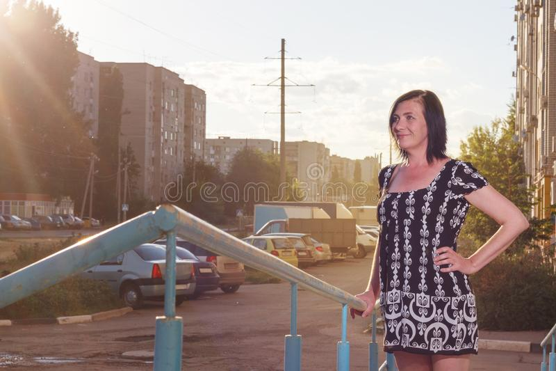 摆在街道上的一个年轻美丽的时兴的愉快的夫人的室外画象 免版税库存图片