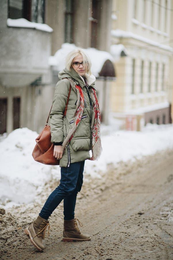 摆在街道上的年轻美丽的愉快的女孩室外画象  式样佩带的时髦的温暖的衣裳 不可思议的降雪 冬天holida 免版税图库摄影