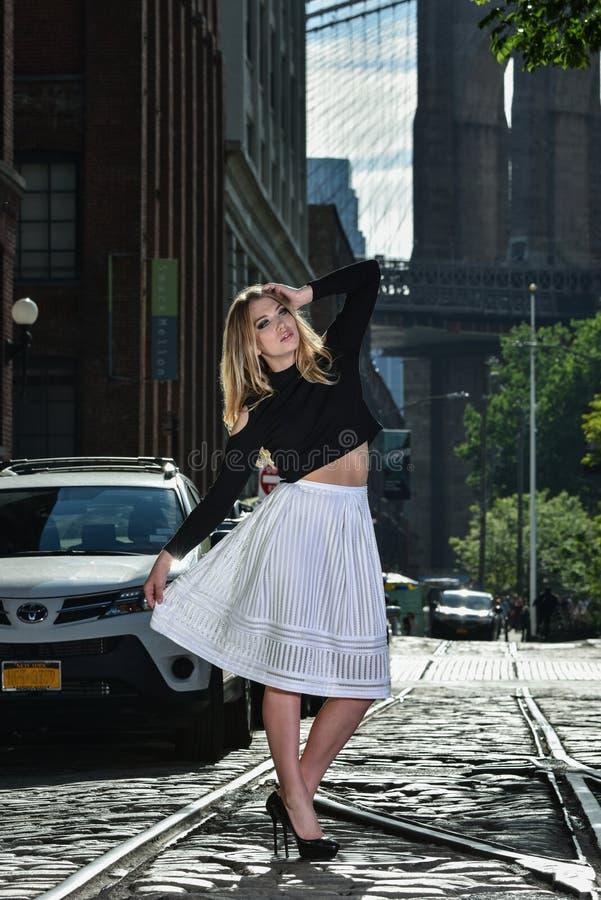 摆在街道上的年轻时装模特儿 免版税库存照片