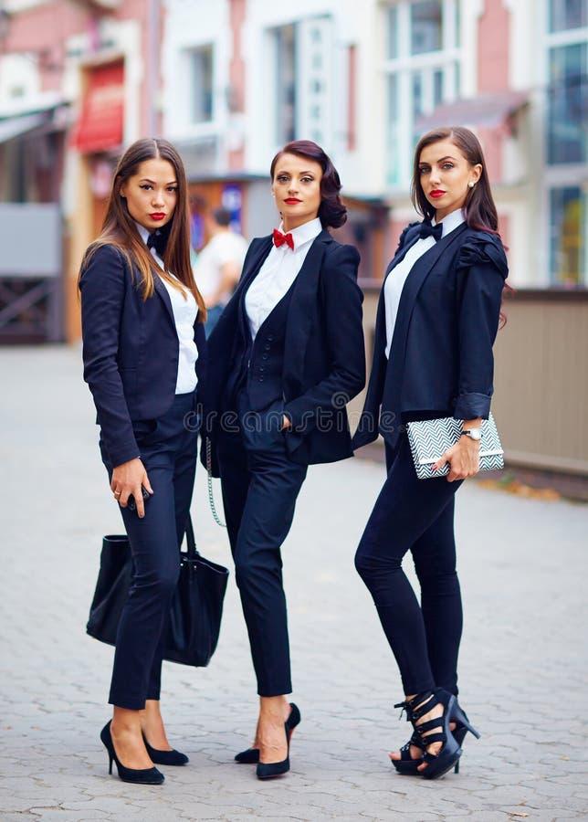 摆在街道上的黑衣服的美丽的女孩 免版税库存图片