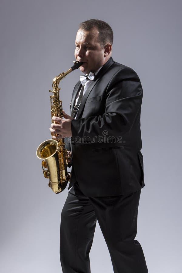 摆在衣服的成熟传神萨克管演奏员 免版税图库摄影