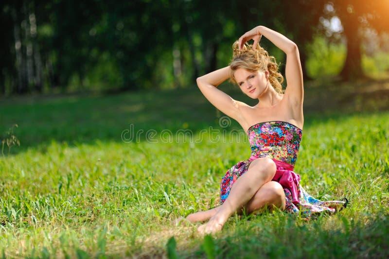 摆在说谎在草的明亮的五颜六色的礼服的年轻白肤金发的女孩在明亮的太阳光芒的夏天公园  免版税库存照片