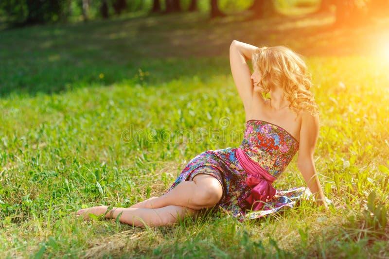 摆在说谎在草的明亮的五颜六色的礼服的年轻白肤金发的女孩在明亮的太阳光芒的夏天公园  免版税库存图片
