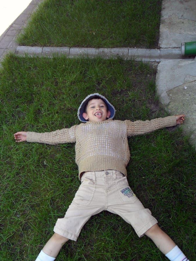 摆在说谎在草的男孩,鬼脸 库存照片