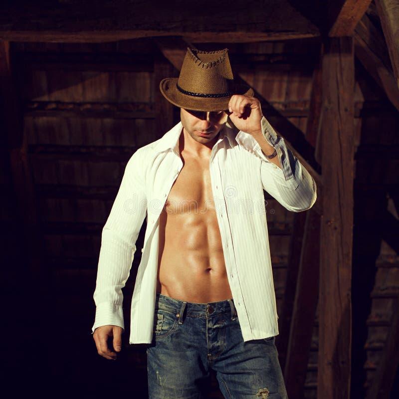 摆在谷仓的帽子和衬衣的性感的人 免版税库存照片