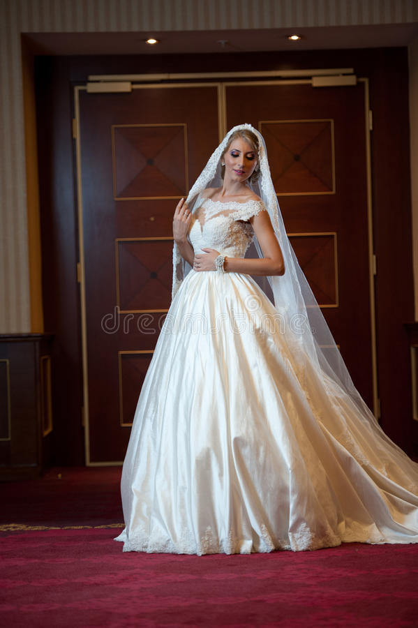 摆在豪华内部的婚礼礼服的年轻美丽的豪华妇女 有长的面纱的华美的典雅的新娘 全长 免版税库存照片