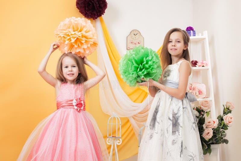 摆在豪华的燕尾服的美丽的姐妹 免版税图库摄影