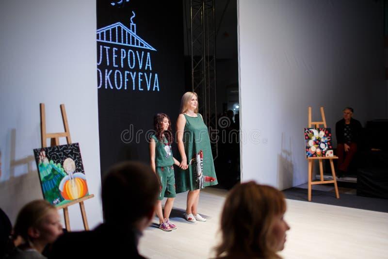 摆在跑道的母亲和女儿在白俄罗斯时尚星期期间 免版税库存照片