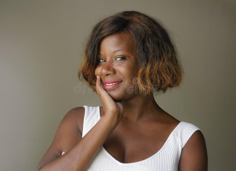 摆在轻松和确信微笑的快乐看的年轻愉快和美丽的黑人非裔美国人的妇女画象  免版税库存图片