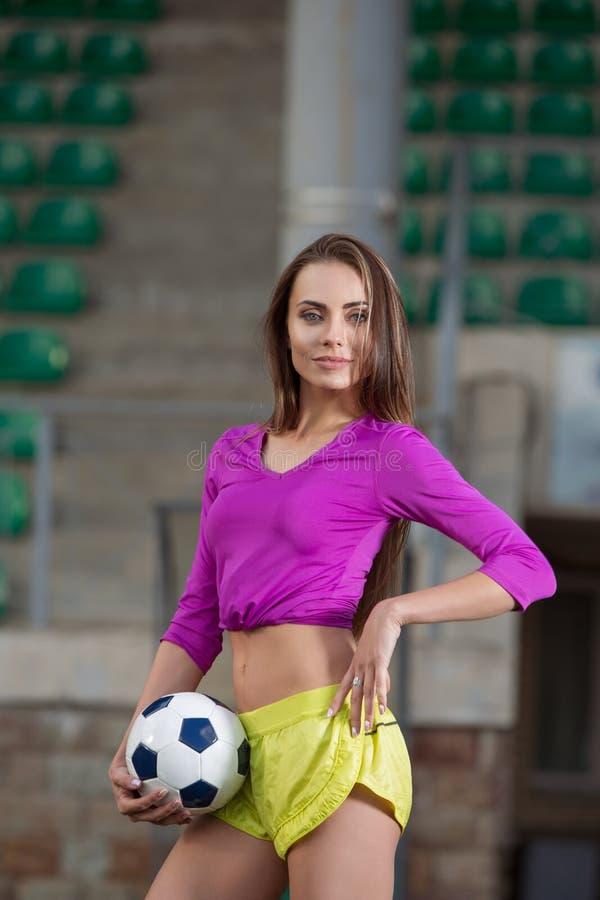 摆在运动场的年轻和美丽的健身妇女 免版税库存照片