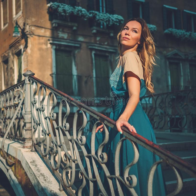 摆在运河的一座桥梁的美丽的穿着体面的妇女在威尼斯 库存图片