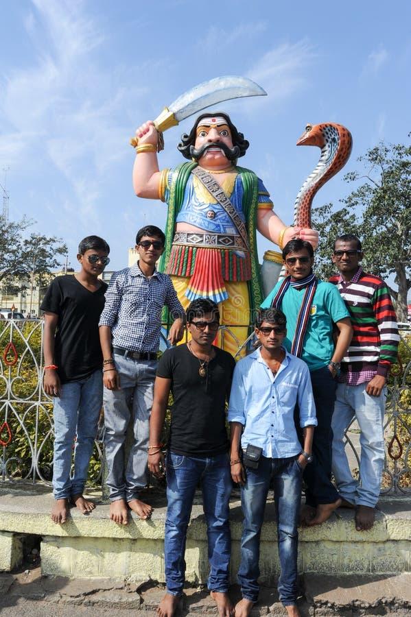 摆在邪魔Mahishasura雕象前面的人们 库存照片