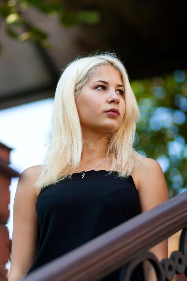 摆在都市风景的背景的年轻美丽的白肤金发的女孩 一件黑礼服的性感的夫人有宜人的 库存照片