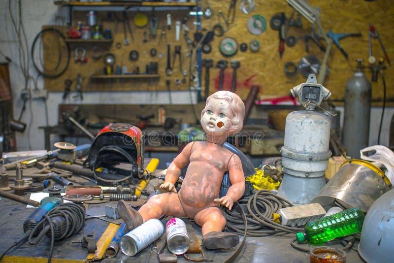 摆在金属商店里面的肮脏的塑料娃娃 免版税库存图片