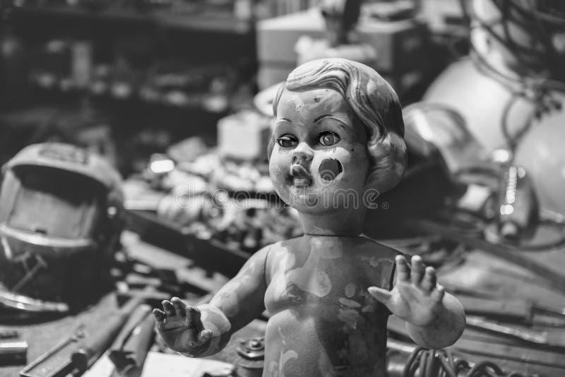 摆在金属车间里面的肮脏的塑料娃娃 库存图片