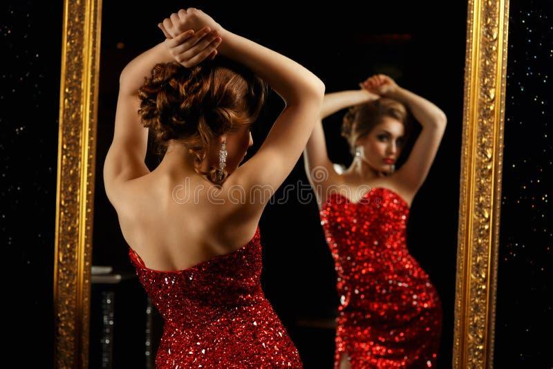 摆在镜子前面的时髦的女人 库存照片