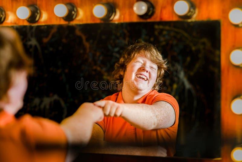 摆在镜子前面的红发男孩 免版税库存照片