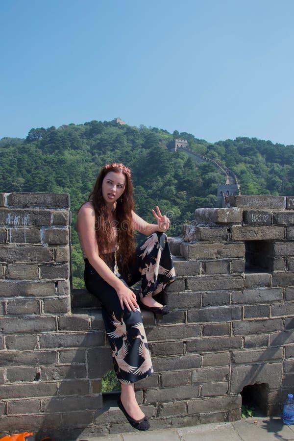 摆在长城的时兴的女性白种人游人 免版税库存照片