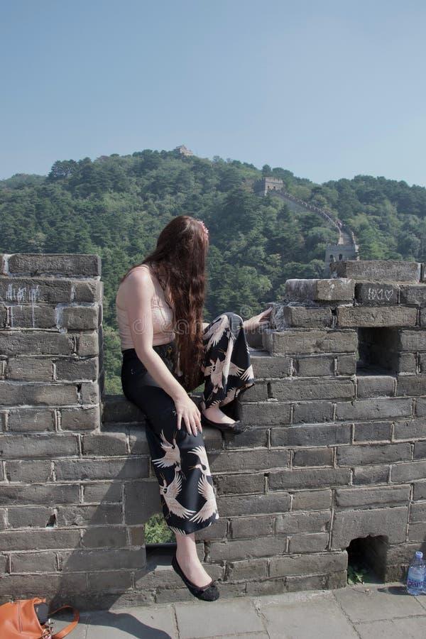 摆在长城的时兴的女性白种人游人 库存照片