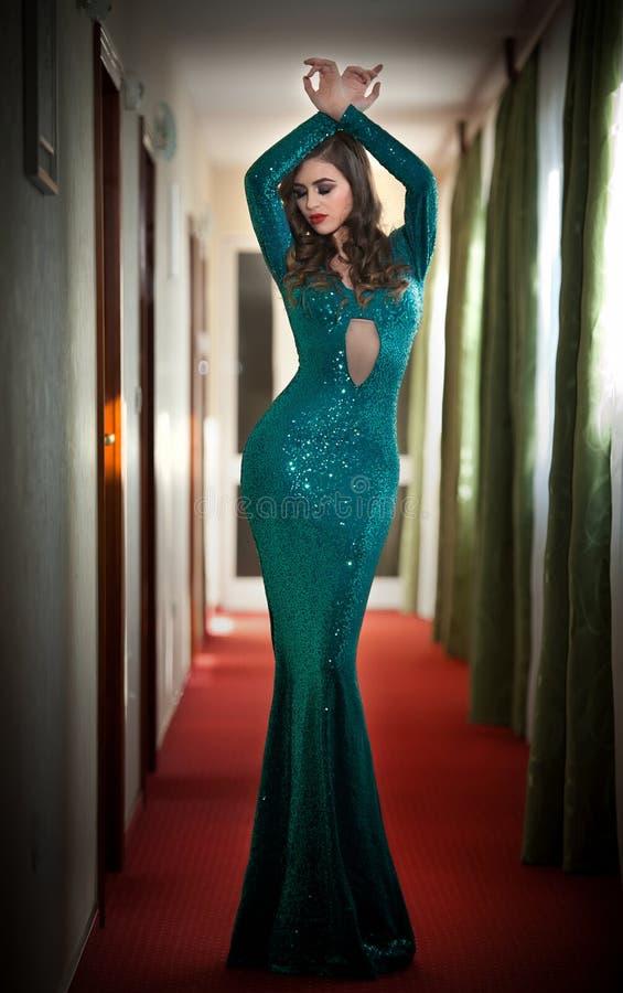 摆在长的典雅的绿松石的礼服的年轻美丽的豪华妇女户内 有紧的适合迷人的礼服的可爱的浅黑肤色的男人 免版税库存照片