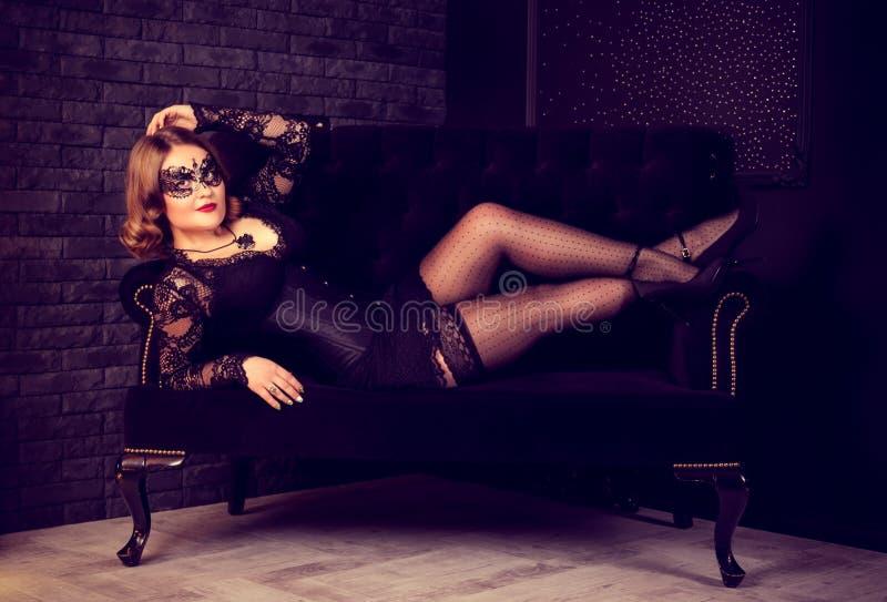 摆在长袜和威尼斯式面具的美丽的少妇在沙发 减速火箭的魅力葡萄酒妇女 库存图片