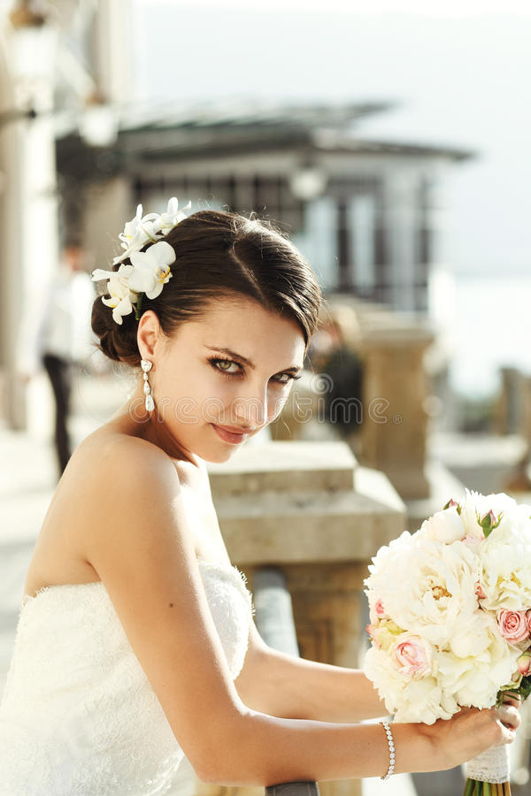 摆在阳台n的白色礼服的情感性感的深色的新娘 免版税库存照片
