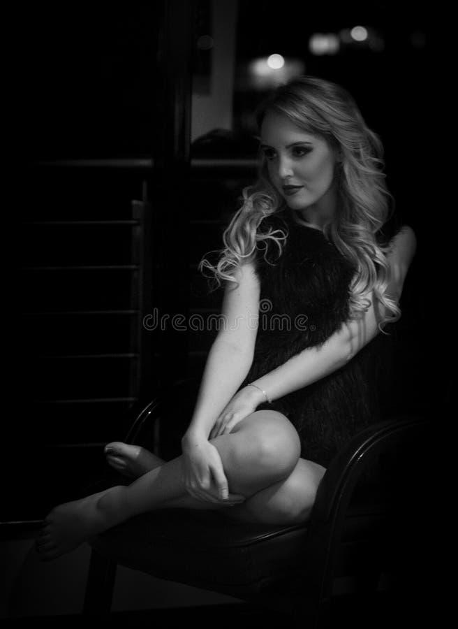 摆在阴影的肉欲的白肤金发的妇女在晚上 图库摄影