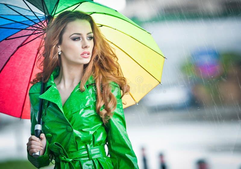 摆在雨中的鲜绿色的外套的美丽的妇女拿着一把多彩多姿的伞 免版税库存图片
