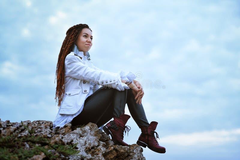 摆在靠近海的Dreadlocks时兴的女孩在日落,坐在天空背景的高石头 免版税图库摄影