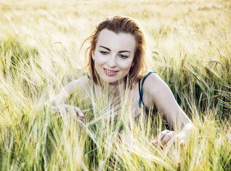 摆在麦子玉米棒的可爱的妇女由日落,自然秀丽 图库摄影