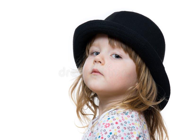摆在黑帽会议的逗人喜爱的小女孩 免版税库存照片