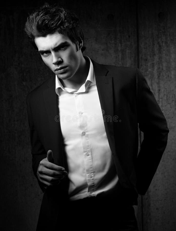 摆在黑时尚衣服和白色的性感的英俊的男性模型 免版税图库摄影