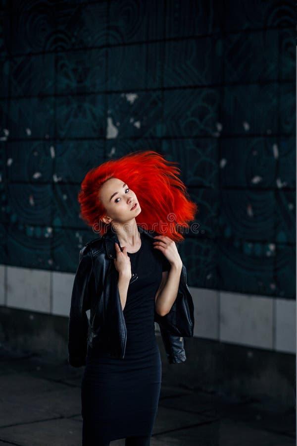 摆在黑暗的墙壁和她的头发飞行的传神红头发人妇女反对黑背景 免版税库存图片
