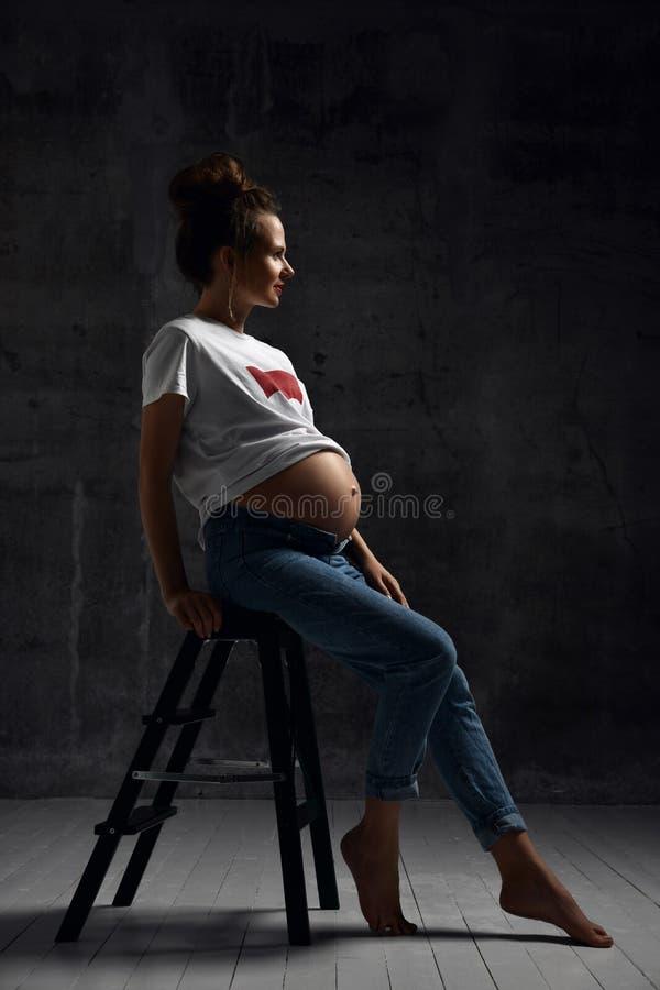 摆在黑暗的白色T恤的美丽的年轻怀孕的愉快的母亲妇女 库存照片