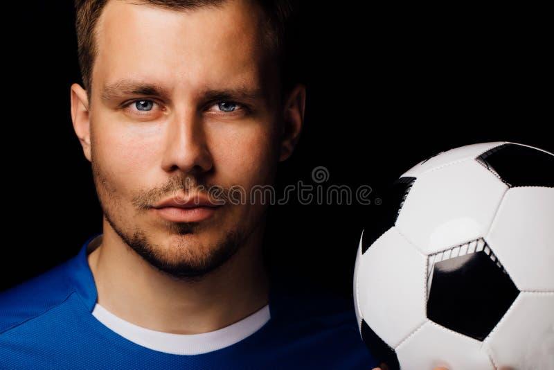 摆在黑暗的背景的年轻英俊的足球运动员足球特写镜头画象  库存照片